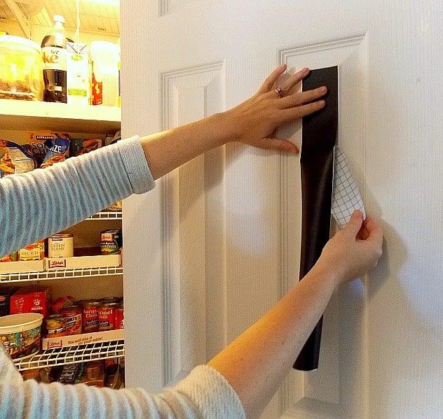 applying chalkboard paper to door of pantry