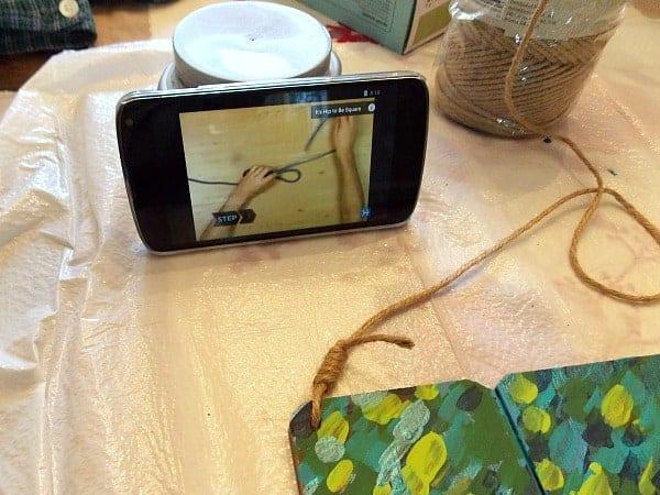 Tying Knots in the jute string holding the door hanger.