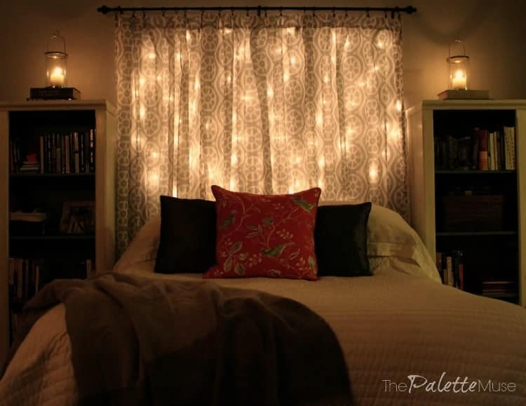 Bed with headboard made of curtains and string lights