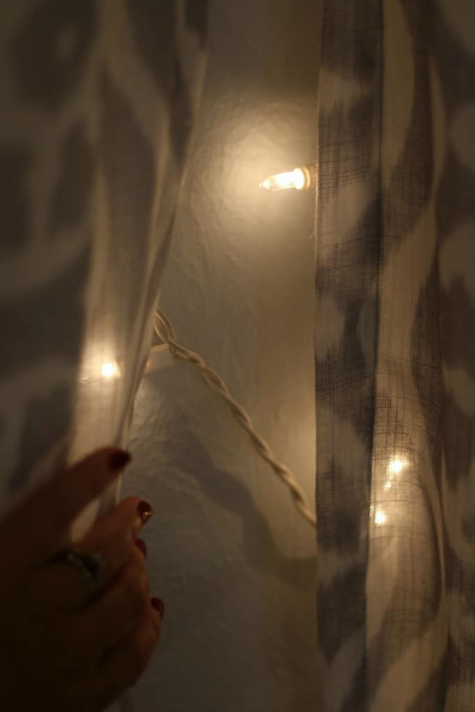 Lit headboard: Hanging curtain in front of the string lights behind the bed