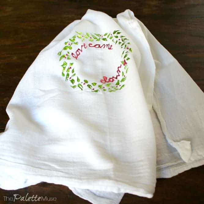 Tea towel decorated with a deco foil wreath in green and pink