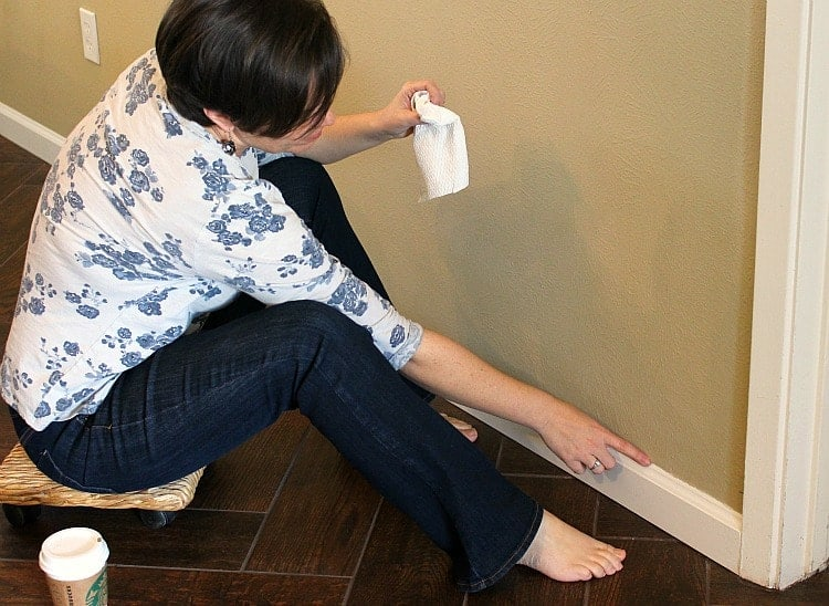 Caulking baseboards using a rolling plant stand to get around easily