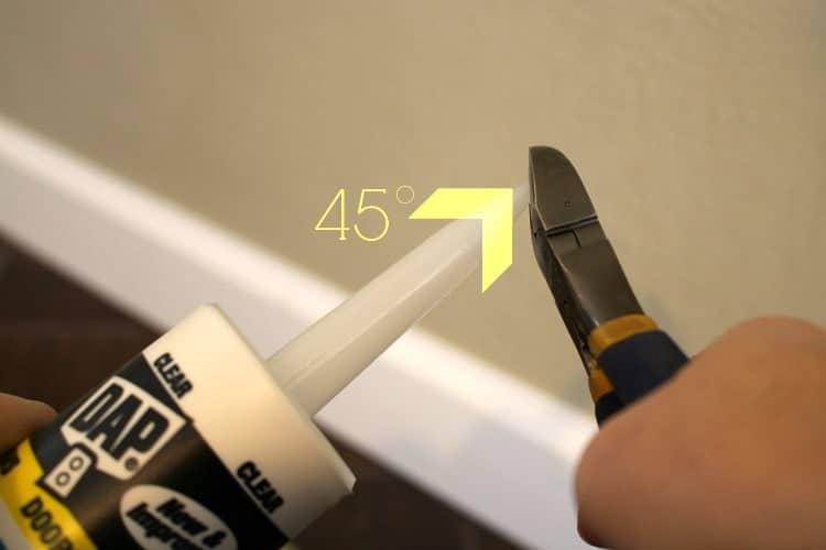 Using wire cutters to cut the tip off a caulk tube at a 45 degree angle