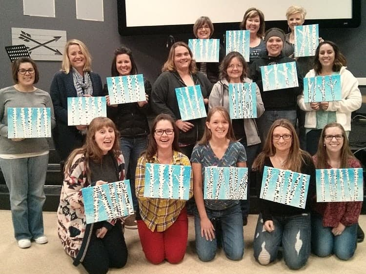 A group of paint party participants with their finished paintings