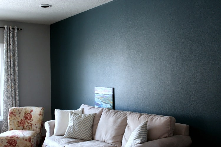 Dark teal wall behind couch, next to gray wall.
