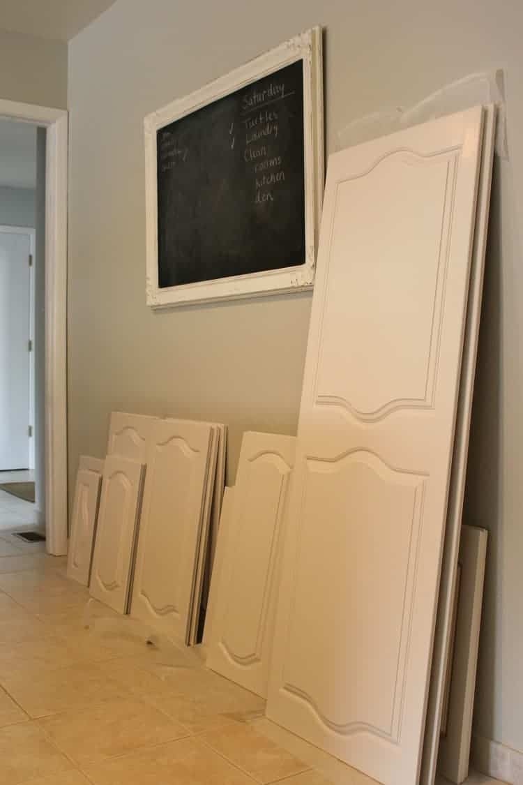 White painted kitchen cabinet doors leaning on the wall to dry