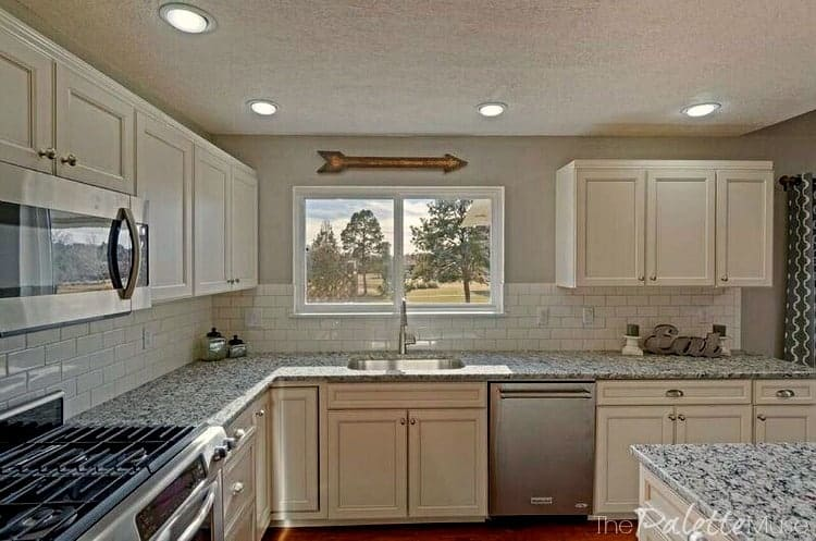 Home staging with a white kitchen and gray granite countertops