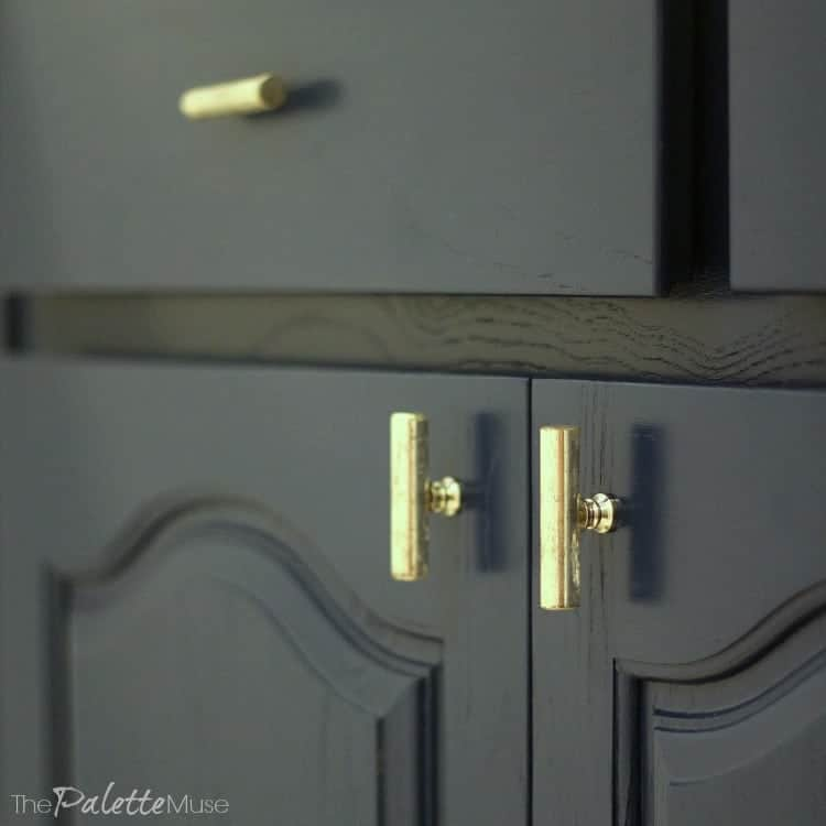 Dark blue painted cabinets with gold pulls.