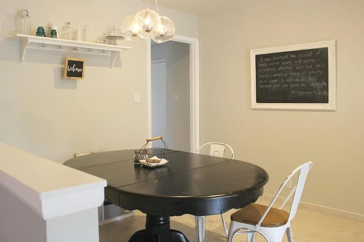 breakfast nook with black table, white chairs, and chalkboard on wall