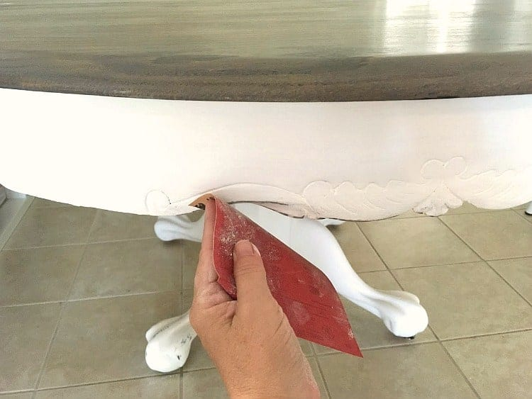 Sanding the edges of a white chalk painted table