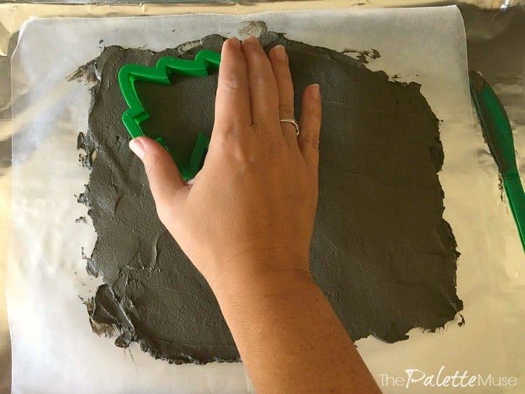 Pressing cookie cutter into wet concrete to make ornaments