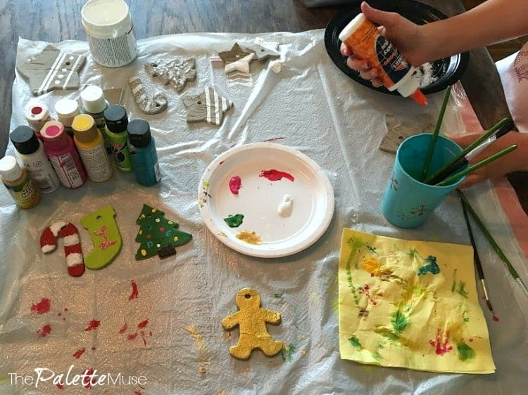 Decorating concrete ornaments with craft paint, glitter, and glue.