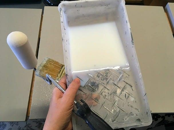 Getting ready to paint bookshelves with polycrylic, roller, and brush in hand