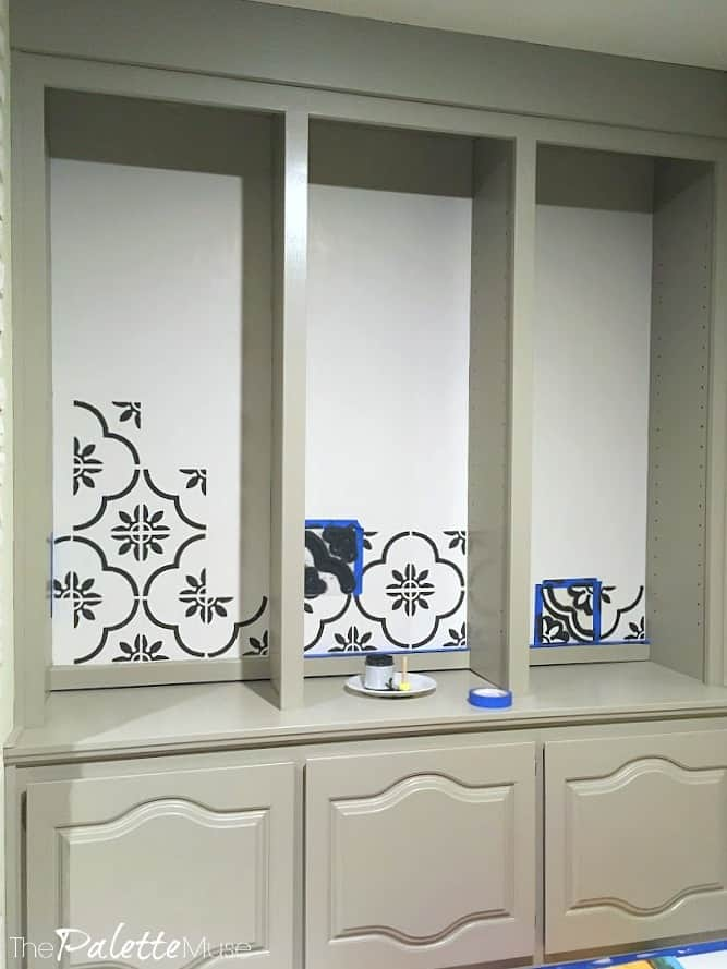 Black and white tile stencil on the wall behind gray bookshelves