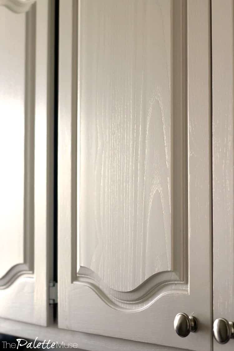 White painted kitchen cabinets detail of wood grain.
