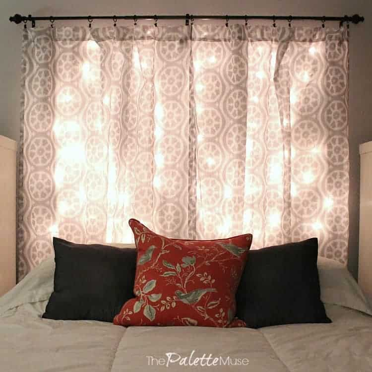 A lit headboard made from curtains and Christmas lights hangs over the bed.