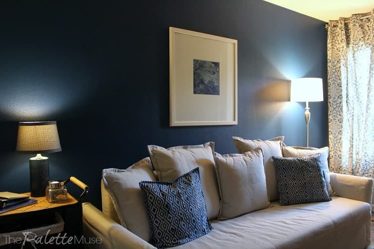 A dark blue accent wall makes this guest room/home office feel cozy and masculine.