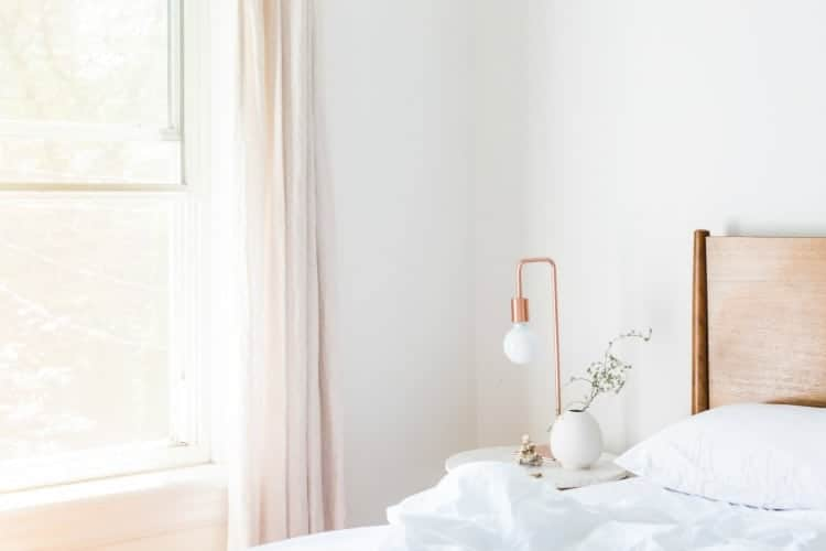 Clean white bedroom with bed and bedside table