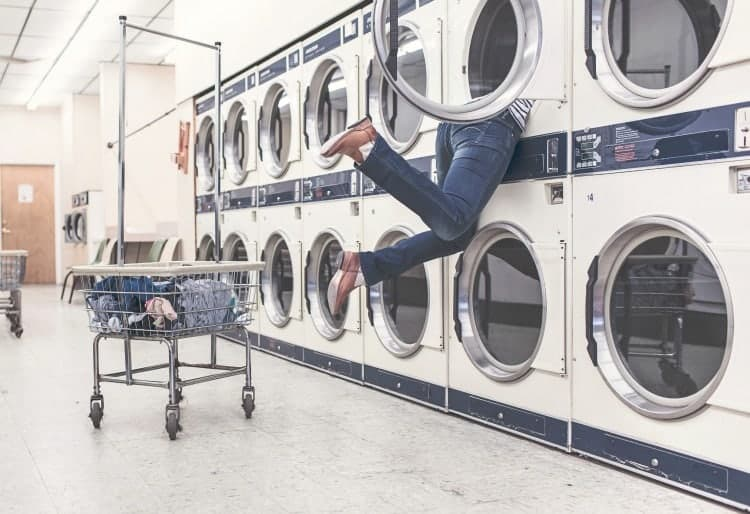 Woman getting sucked into laundry machine
