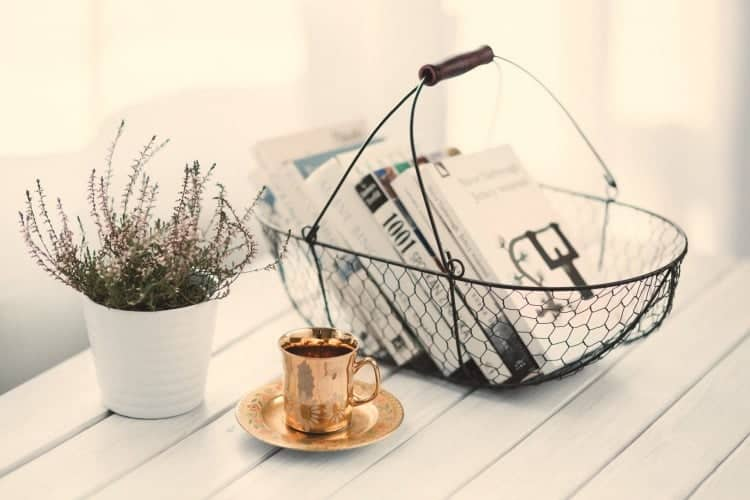 A basket of books, plant, and cup of tea are the perfect way to welcome guests to your vacation rental.