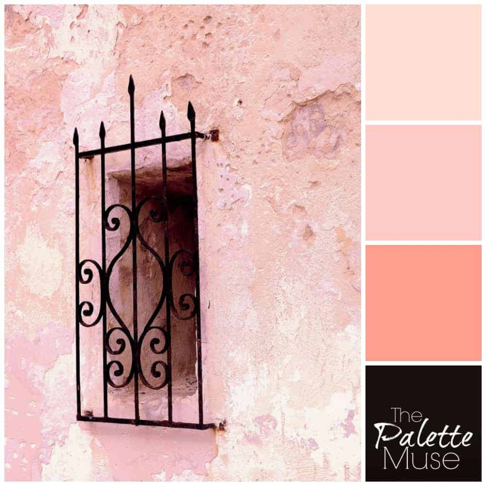A dark window covered with black wrought iron peeks out of a layered pink plaster wall.
