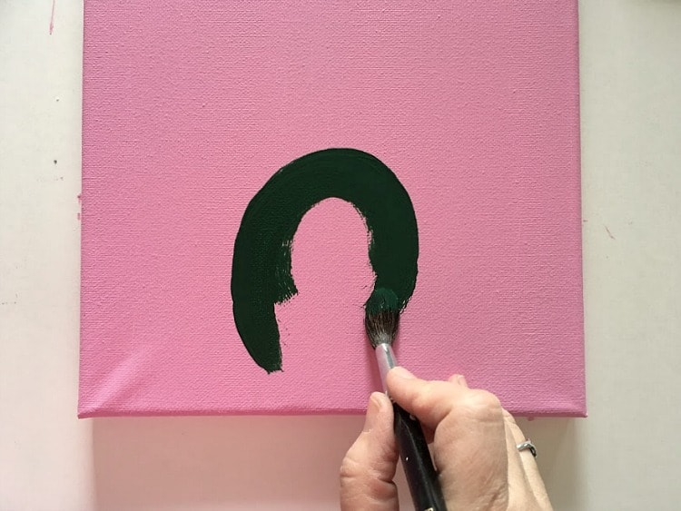Painting the beginning of a green cactus on a pink background