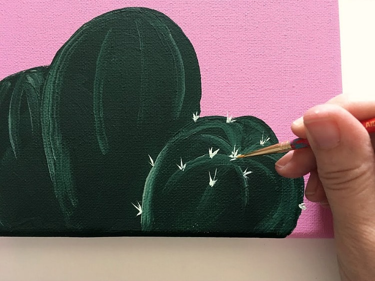 Painting white cactus spikes on a green and pink cactus painting.