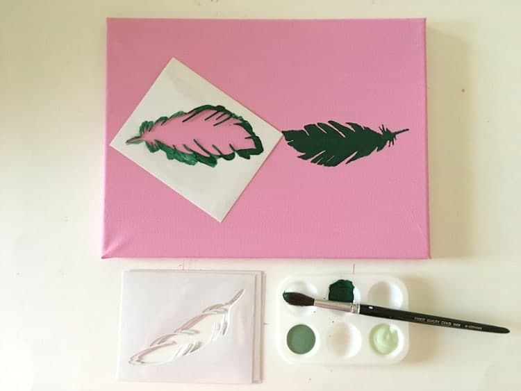 Using a stencil to paint a green feather on a pink background.