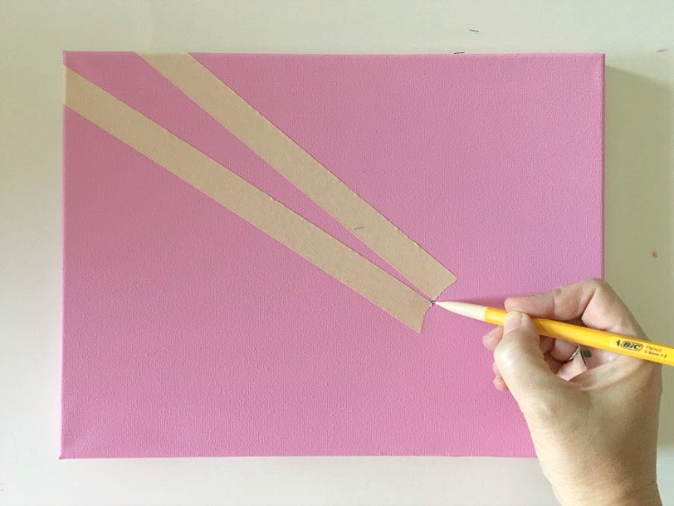Masking tape forms a ray on a pink canvas