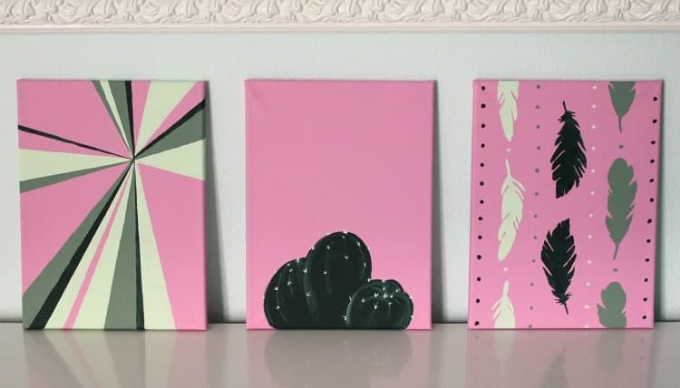 Three pink and green paintings lined up on the wall.