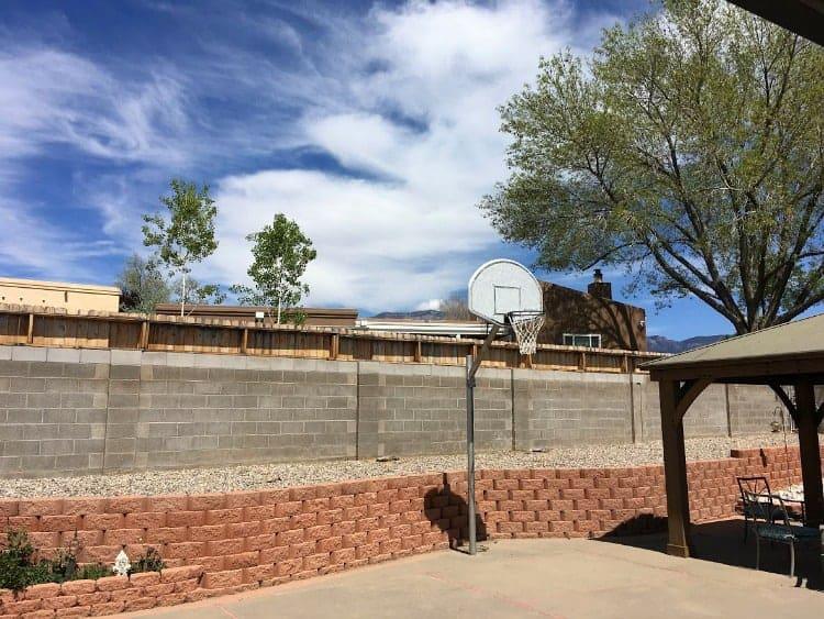 A concrete block wall surrounds a yard and concrete patio.