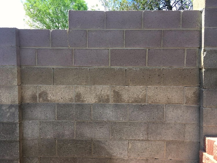 Concrete block wall with three different colors of blocks built up over years