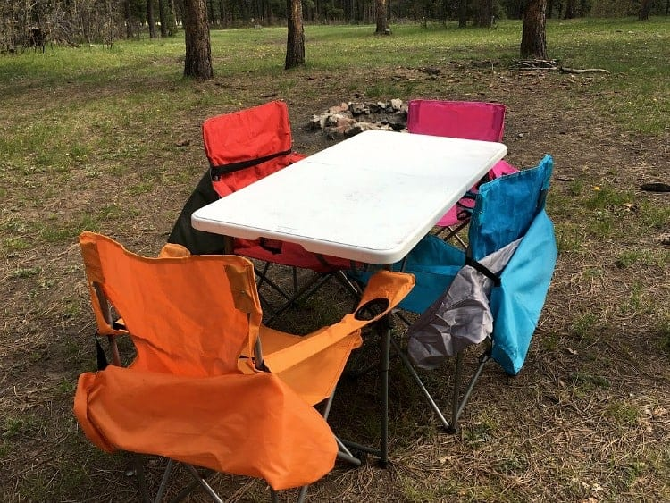 Use a larger folding table and folding chairs for eating dinner while camping.