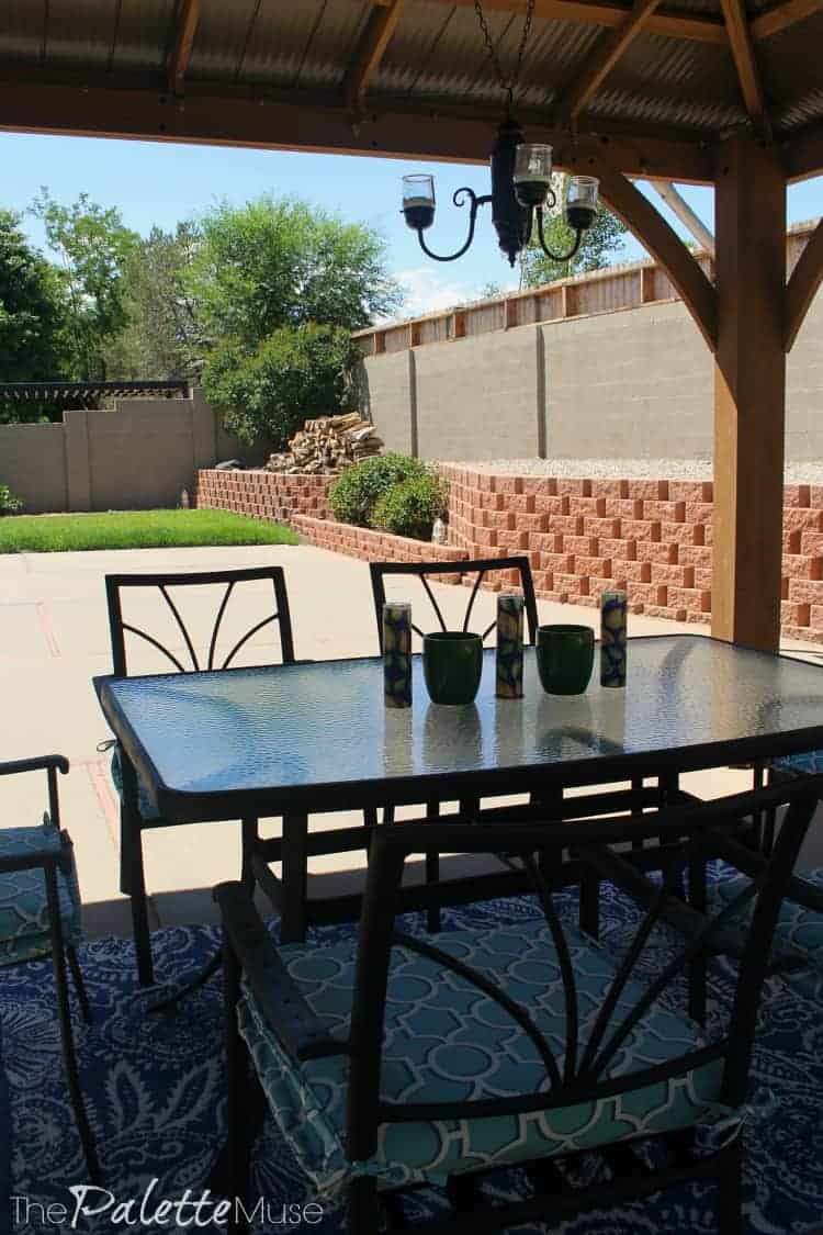 A gazebo and shaded dining set against a background of painted concrete wall.