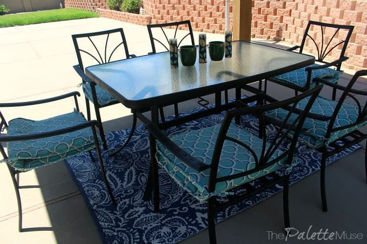 Black wrought iron dining set with blue cushions.