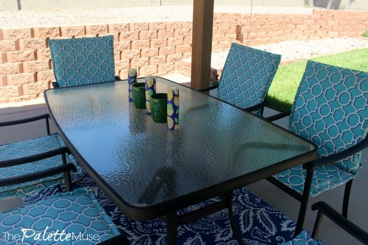 Light blue chair covers and a dark blue rug make this outdoor patio feel like a part of the home.
