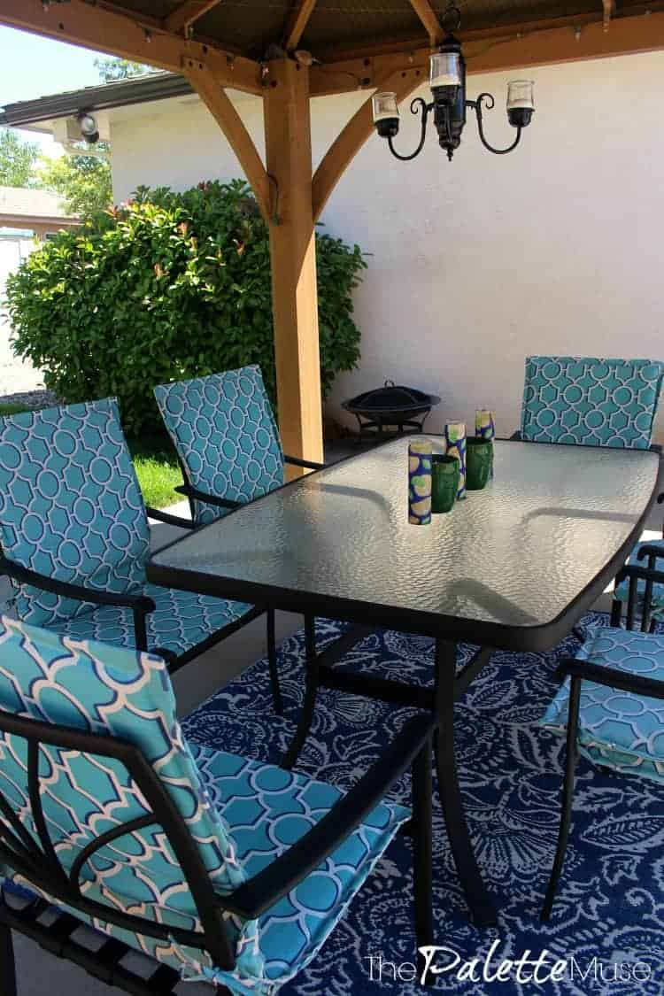 A gazebo provides shade for a blue outdoor dining table and chairs.