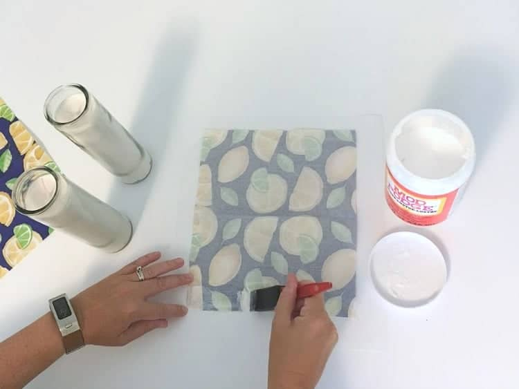 Applying a strip of ModPodge glue to the front edge of the napkin.