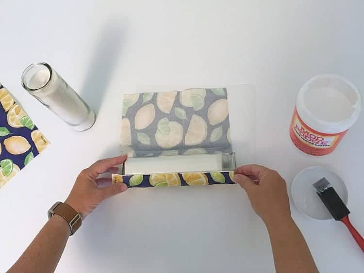 Rolling the napkin onto the candle with glue.
