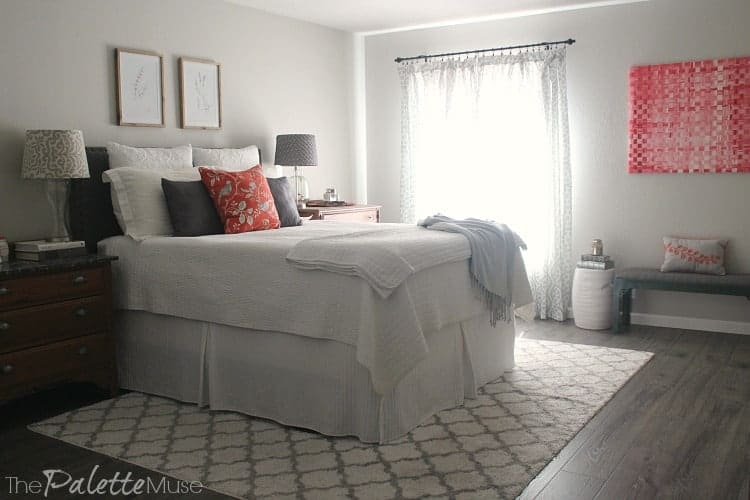 A gray and white bedroom with bright accents of pink and orange.