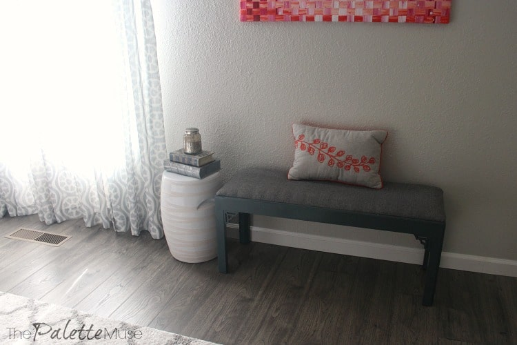 Dark gray upholstered bench and white garden stool