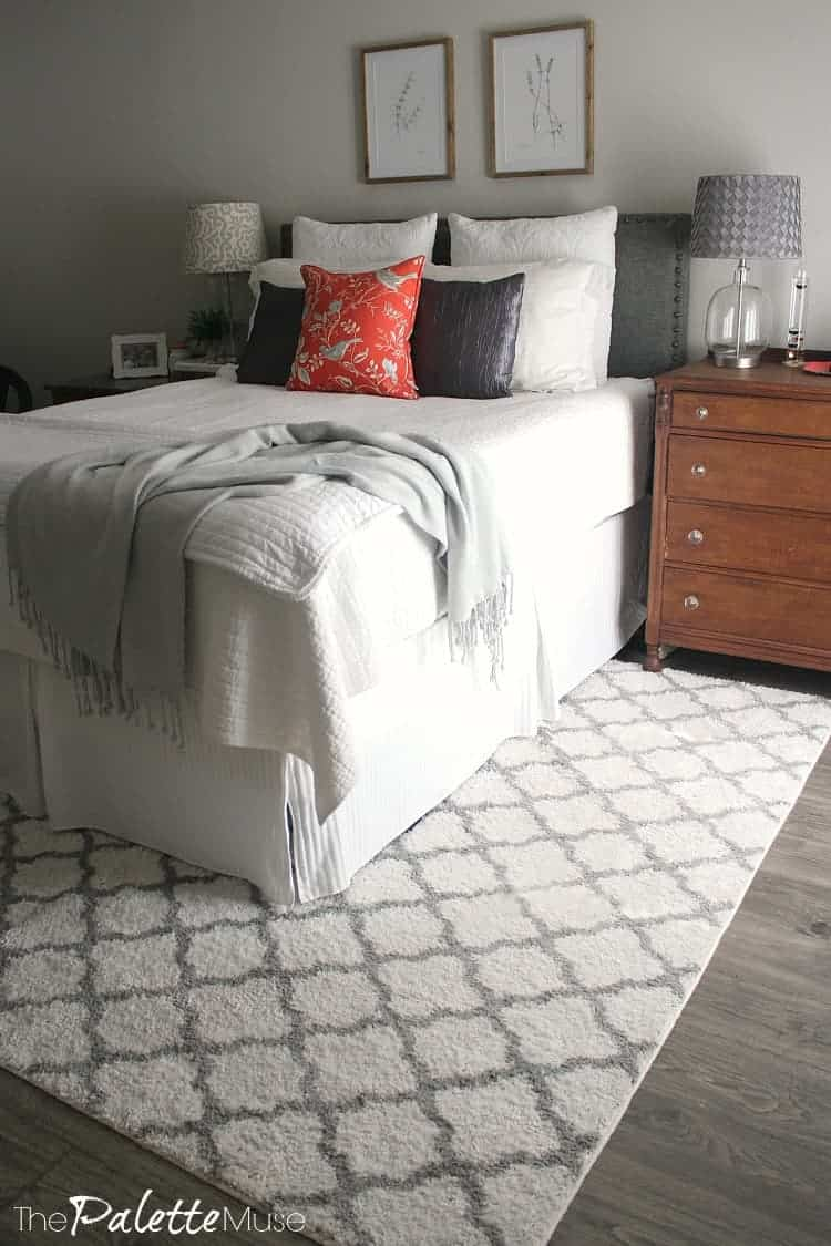 White bed on white and gray trellis rug.