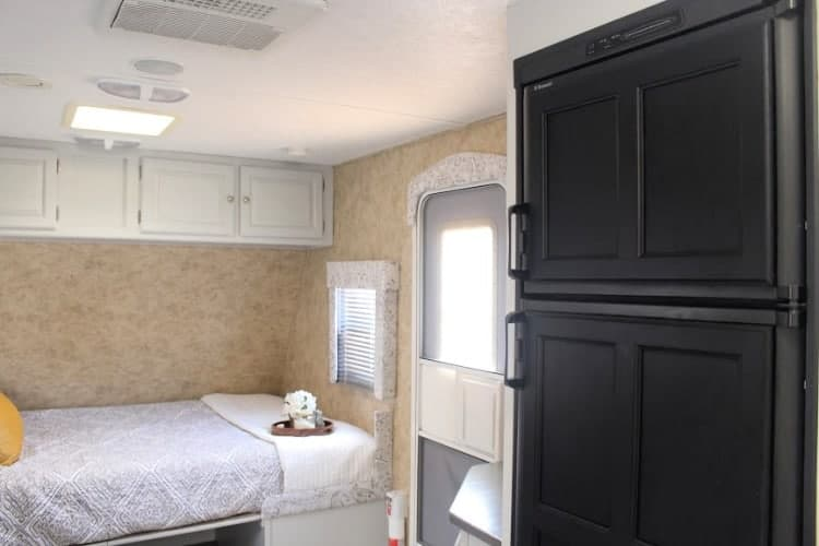 Camper interior with black refrigerator in foreground.
