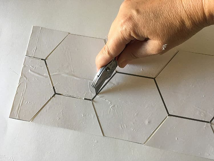 Using an X-acto knife to cut out stencil