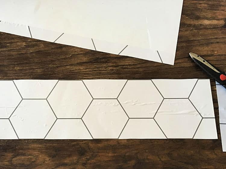Strips of wallpaper and posterboard are being cut to make a stencil
