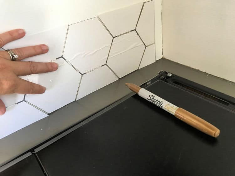 Holding the stencil up to the wall