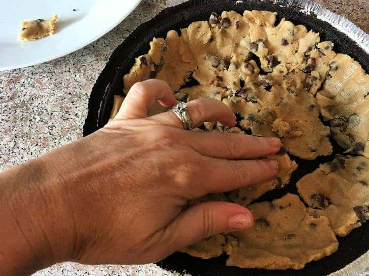 Mushing the chocolate chip cookie dough into the oreo pie crust for brownie pie.