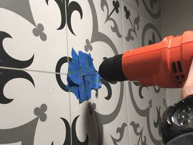 Drilling into tile which has been covered with blue tape to prevent chipping.