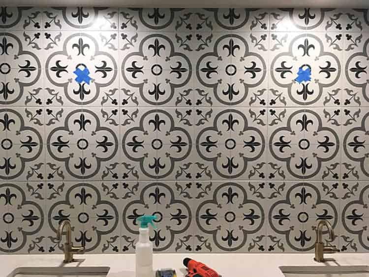 Patterned tile backsplash before hanging mirrors. Blue tape marks the spot.