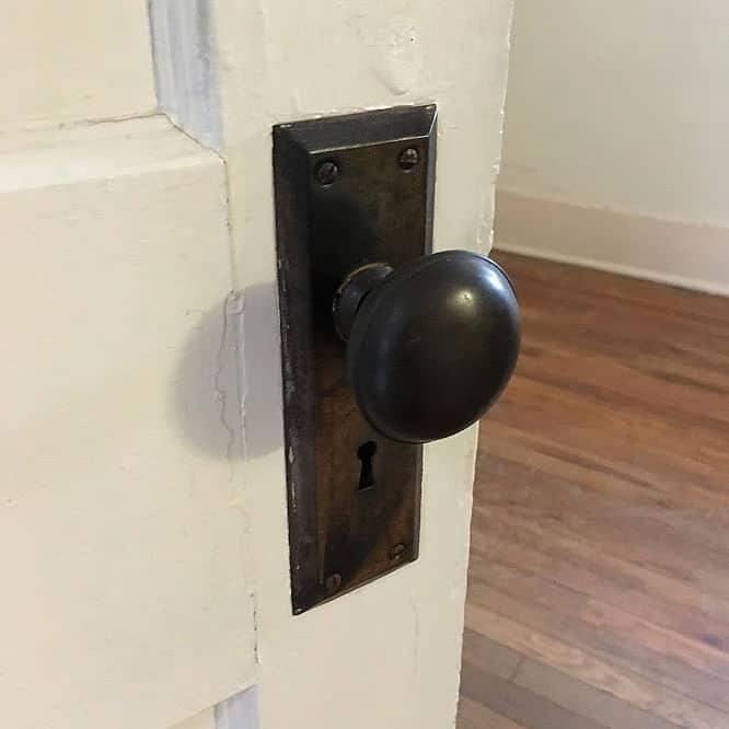 Vintage bronze door knob and plate on white door